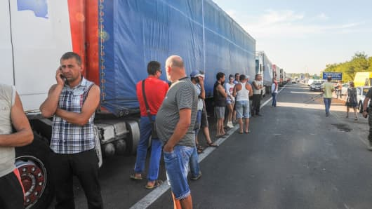 Trucks queue after Tatar activists block a road near to the border crossing point into Crimea
